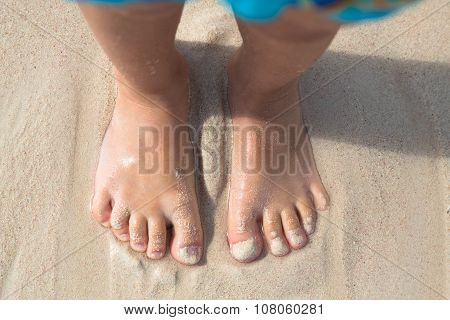 Bare feet little kid stand on the beach, top view