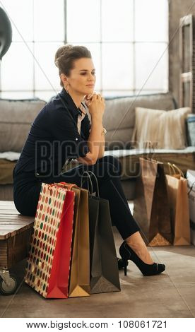 Dreamy Brown-haired Woman With Shopping Bags In Loft Apartment