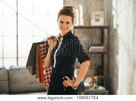 Elegant Brunette Woman Holding Shopping Bags In Loft Living Room