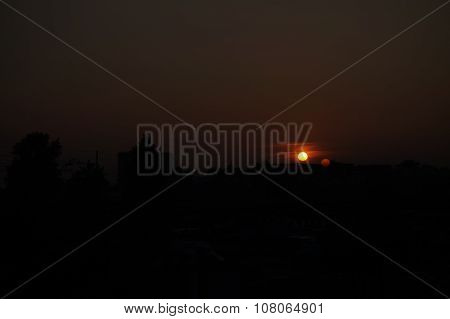 Red sunset with a reflection of the sun with contrasty and black city landscape