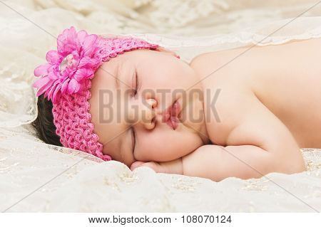 Newborn baby girl sleeping on stomach