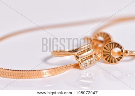 Elegant gold earrings and a ring from the same set amid gold snake chain weave