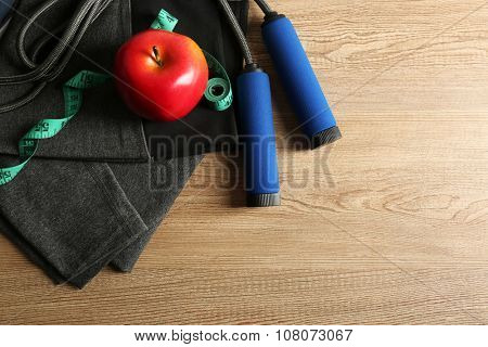 Sport shoes, clothes, equipment and smart phone with headphones on light background