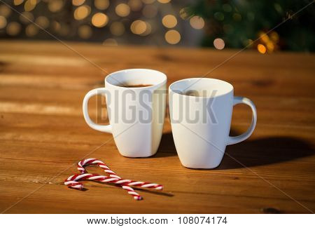 holidays, christmas, winter, food and drinks concept - close up of candy canes and cups with hot chocolate or cocoa drinks on wooden table over christmas tree lights