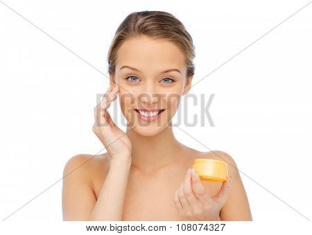 beauty, people, cosmetics, skincare and cosmetics concept - happy young woman appying cream to her face