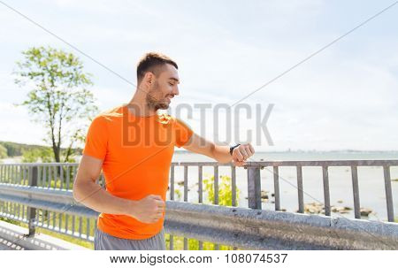 fitness, sport, people, technology and healthy lifestyle concept - smiling young man with smart wristwatch at summer seaside