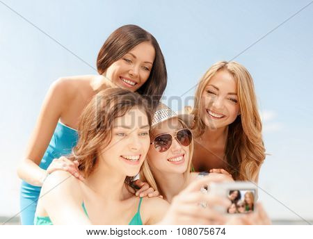 summer holidays and vacation concept - smiling girls taking photo in cafe on the beach