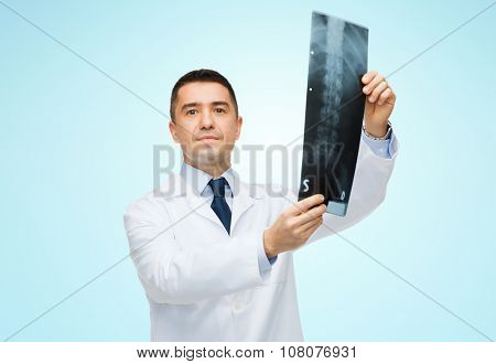 healthcare, rontgen, people and medicine concept - male doctor in white coat holding x-ray over blue background