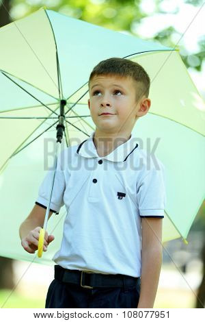 Boy under big creamy umbrella at the park