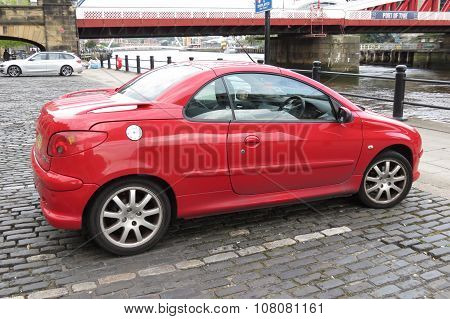 NEWCASTLE UK - CIRCA AUGUST 2015: red Peugeot 206 car (new model) parked in a street