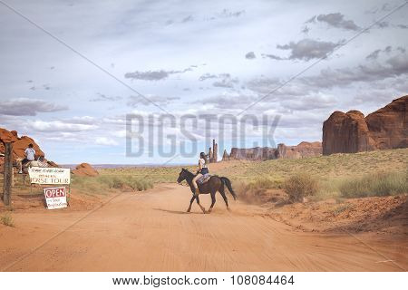 Tourist Riding Horse In Navajo Nation's Monument Valley Park.