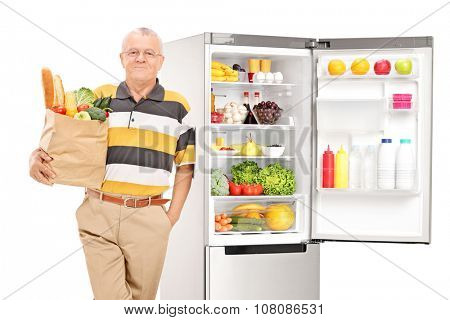 Mature man holding a grocery bag by an open fridge isolated on white background