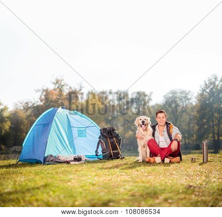 Young male camper sitting on grass and hugging his pet dog next to a blue tent on a beautiful autumn day shot with tilt and shift lens