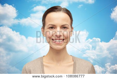 female, gender, portrait and people concept - smiling young woman in cardigan over blue sky and clouds background