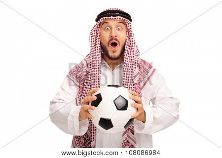 Surprised young Arab in a white robe holding a football and looking at the camera isolated on white background