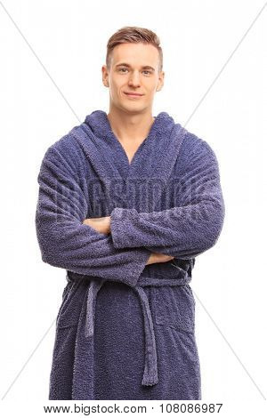 Vertical shot of a cheerful young man in a blue bathrobe smiling and looking at the camera isolated on white background