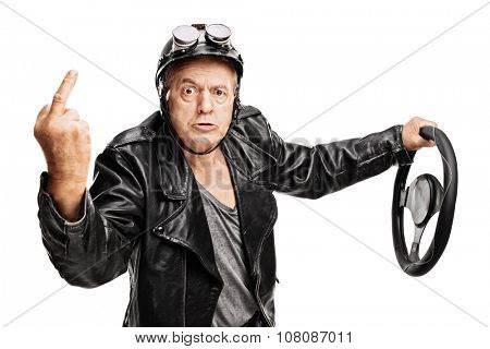 Studio shot of an angry senior driver showing a middle finger and holding a steering wheel isolated on white background