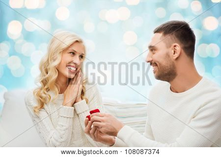 love, couple, relationship, proposal and holidays concept - happy man giving engagement ring in little red gift box to woman over blue holidays lights background