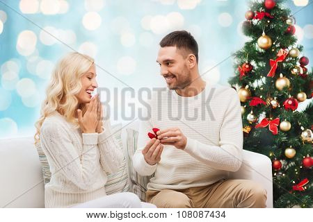 love, christmas, couple, proposal and people concept - happy man giving engagement ring in little red box to woman over blue holidays lights background