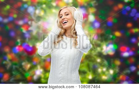 winter, fashion, christmas and people concept - smiling young woman in earmuffs and sweater over holidays lights background
