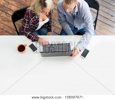 Students sitting at the table using laptop.