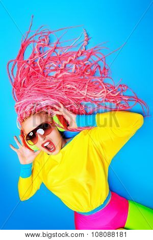 Crazy expressive trendy DJ girl in bright clothes, headphones and bright dreadlocks. Disco, party. Bright fashion.