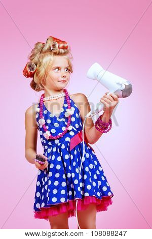 Portrait of a cute funny little pin-up girl in hair curlers with a hairdryer in the hand. Pink background.