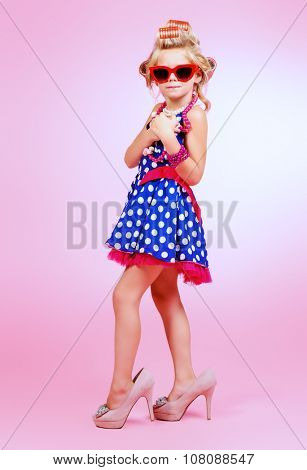 Cute little pin-up girl singing with a microphone. Pink background.