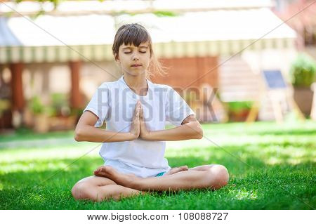 Little girl meditating while sitting in lotus position