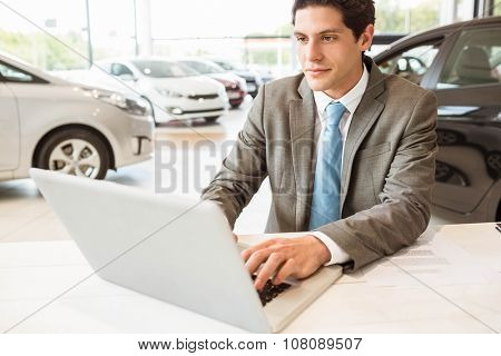 Smiling salesman writing on his laptop at new car showroom