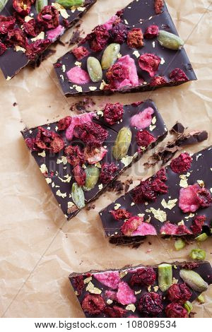 Handmade chocolate with berries, pistachios and edible gold