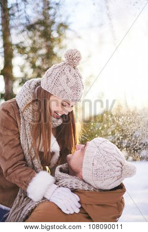 Happy couple playing together outdoors in winter