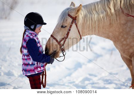Little girl with horse outdoor in winter