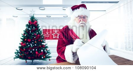 Santa writes something with a feather against home with christmas tree