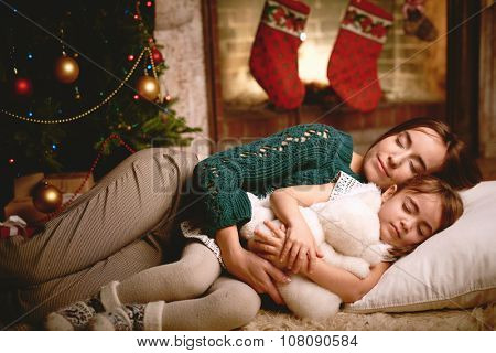 Cute girl with teddybear and her mother sleeping on Christmas evening