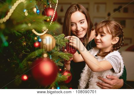 Cute girl and her mother decorating firtree on Christmas eve