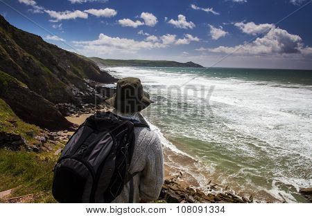 Male with rucksack hiking in rugged coastal panorama.