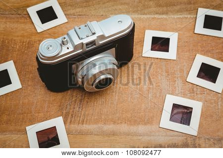 View of an old camera with photo slides on wood desk