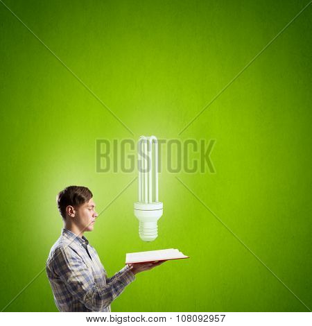 Young man with opened book and bulb on it on color background