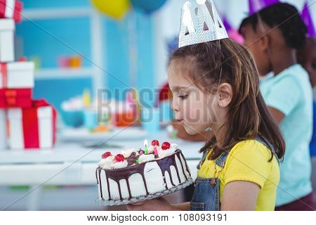 Smiling girl holding birthday cake at the birthday party