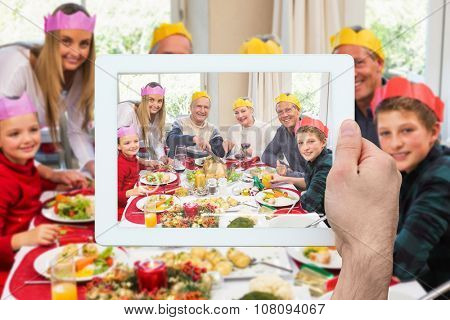 Hand holding tablet pc against grandfather in party hat carving chicken during dinner