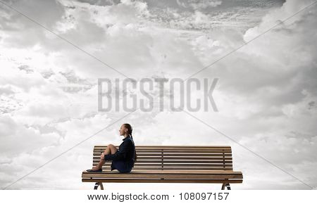 Bored young businesswoman sitting alone on wooden bench