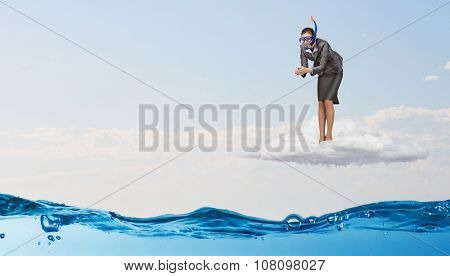 Young businesswoman in suit and diving mask jumping in water