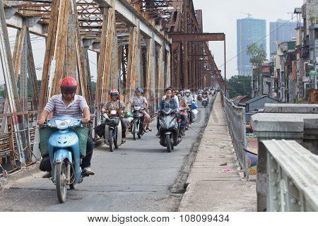 Vietnamese people riding motorcycles on Long Bien bridge over Hong (Red) river