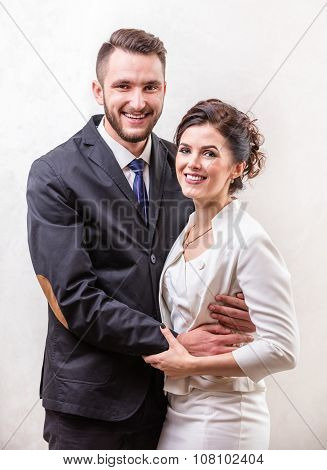 Cheerful young couple smiling over white