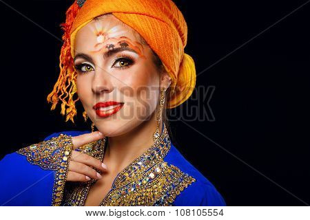 Portrait Of Oriental Beauty In A Turban And Face Art.