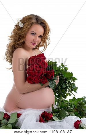 Nude pregnant woman posing with rose bouquet