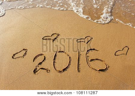 2016 year and heart written on sandy beach sea