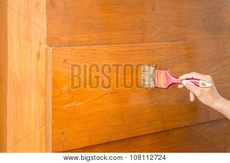 Hand Holding Brush Nd Painting On The Wooden Door
