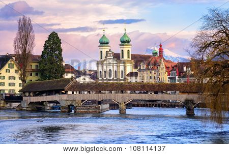 Lucerne, Switzerland, View Over The Reuss River To The Wooden Spreuer Bridge, Jesuit Church And The
